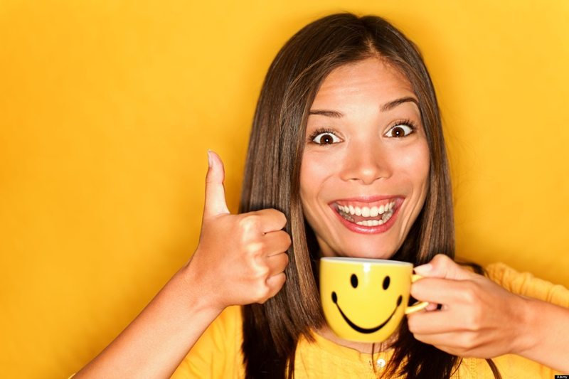 D2W9YA Portrait of beautiful young multiracial Caucasian / Chinese Asian woman drinking coffee giving thumbs up on yellow background